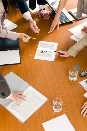 Afbeelding van meerdere handen wijzen op document op zakelijke conferentie  Stockfoto