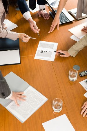 Image of several hands pointing at document at business conference