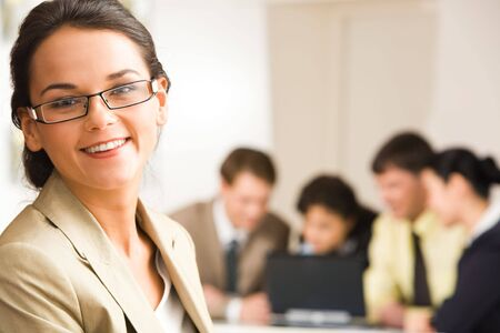 foreground: Portrait of confident woman in glasses on the background of working business people