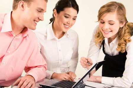 Photo of smart professional pointing at laptop screen while two colleagues looking at it with smiles photo