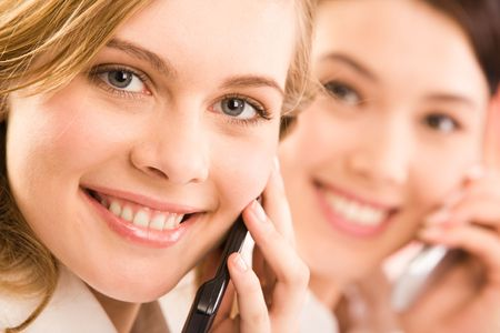 Close-up of pretty woman with cellular phone looking at camera with smile photo