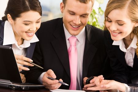 Photo of young businessman between two smart women pointing at document during meeting photo