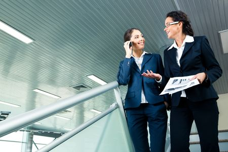 downstairs: Photo of business ladies walking downstairs and speaking to each other