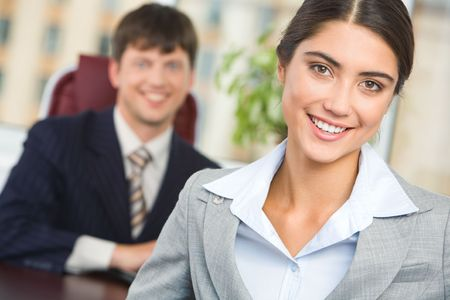 Portrait of happy businesswoman looking at camera on background of confident man photo