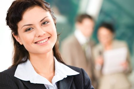 Portrait of pretty employee looking at camera with smile in working environment photo
