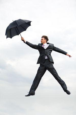 gambe aperte: Immagine di uomo d'affari che vola in aria aperta con ombrello in mano, su sfondo di cielo  Archivio Fotografico