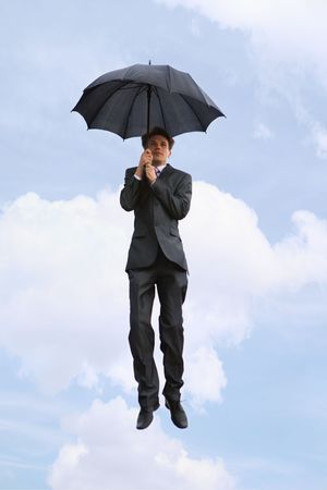 flying man: Portrait of businessman under umbrella on the background of cloudy sky