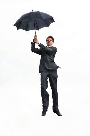 Image of businessman holding umbrella and flying on a white background photo
