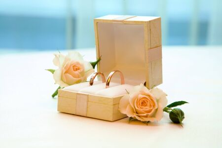 Close-up of two wedding rings in box with roses near by   photo