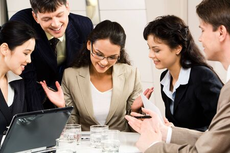 Image of successful businesswoman with four colleagues looking at plan near by  photo