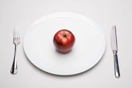 Image of red apple on white plate with fork and knife near by photo