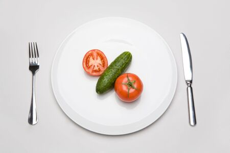 Photo of tomatoes with cucumber placed on the white plate photo