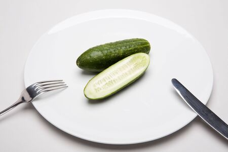 Photo of cucumbers placed on the plate with fork and knife near by photo