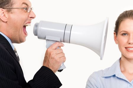 Portrait of businessman holding megaphone shouting straight into woman�s ear photo