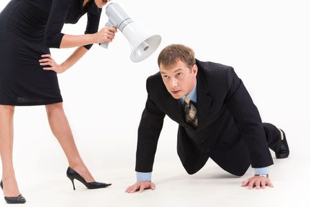 Image of businessman in suit doing physical exercise while standing woman shouting at him through loudspeaker photo