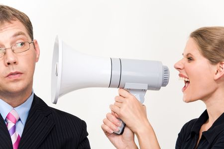 Close-up of young furious woman screaming at her boss through megaphone  photo