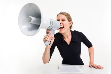 agitation: Portrait of businesswoman sitting at the table and speaking through megaphone  Stock Photo
