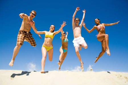 Image of five energetic people jumping at the beach