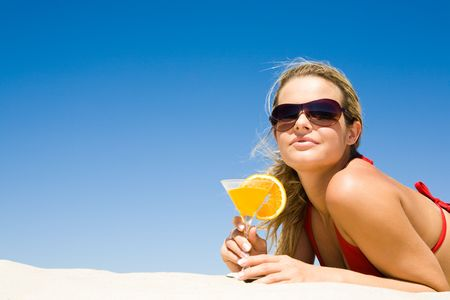 idling: Portrait of relaxing woman wearing sunglasses with glass of cocktail in hand lying on sand