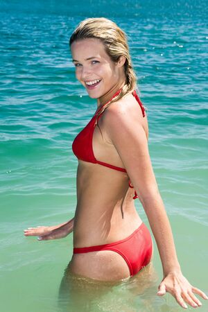Image of happy girl standing in the water while her vacation  photo