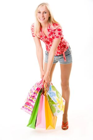 Image of beautiful woman with shopping bags in hand standing in the studio photo