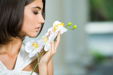 Portrait of young woman smelling a beautiful flower Stock Photo - 3362838
