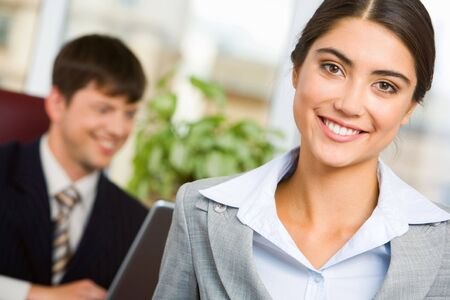 Portrait of smiling businesswoman on background of her working colleague photo