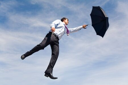 Conceptual photo of businessman flying on his umbrella up into bright blue sky photo