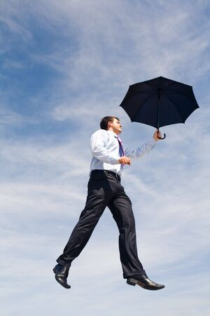 Creative image of businessman with black umbrella flying on the background of sky photo