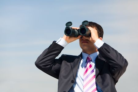 see  visionary: Portrait of confident man in suit observing through binoculars somewhere outside