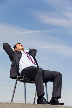 Portrait of sitting businessman with his eyes closed and hands behind head outside at summertime photo