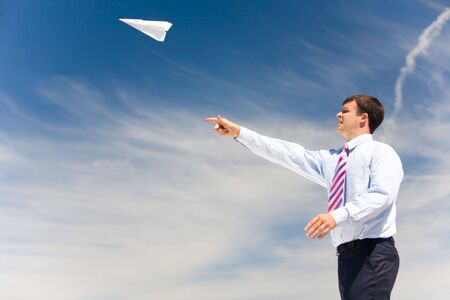 Image of businessman letting paper airplane fly and looking at it on background of blue sky photo