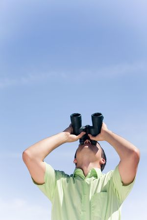 Photo of businessman in casual clothing looking through binoculars  photo