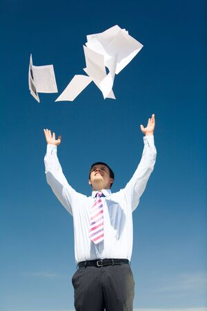 Portrait of successful businessman standing and tossing up papers on background of blue sky photo