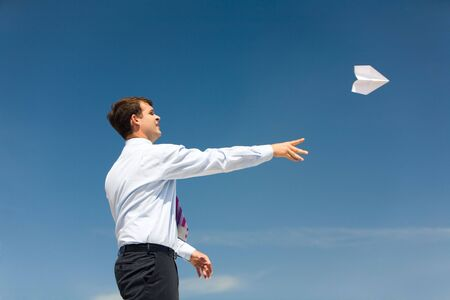 Conceptual photo of businessman standing with his arm stretched after launching paper aeroplane into bright sky