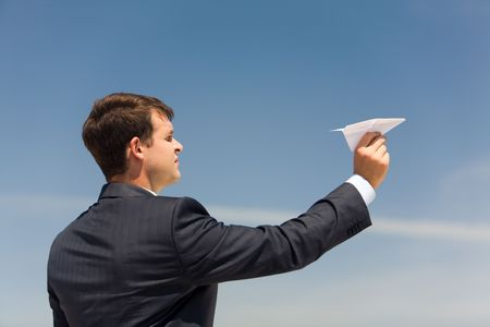 Photo of businessman holding paper aircraft in stretched hand before launching it photo