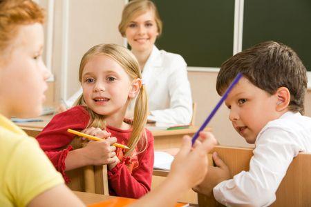 Portrait of schoolchildren sitting in classroom and speaking with their teacher behind photo