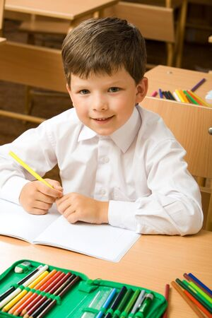 Portrait of cute boy sitting at desk with copybook and colored pencils near by Stock Photo - 3382757