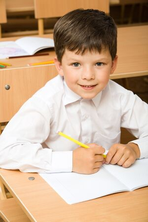 Portrait of pupil wearing white shirt sitting in the classroom and looking at camera Stock Photo - 3382726