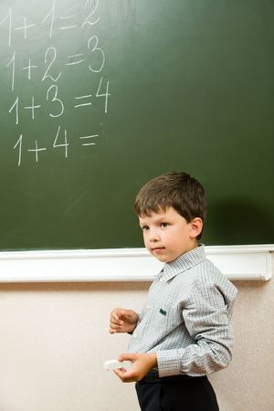 sums: Portrait of pensive schoolchild standing at blackboard and doing sums