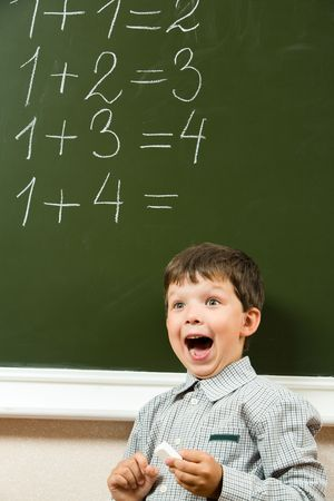 sums: Portrait of happy boy screaming before blackboard with sums on it during lesson