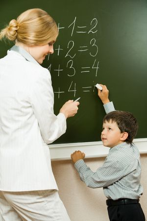 sums: Photo of elementary student doing sums on blackboard and looking at his teacher who is helping him Stock Photo