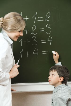 sums: Portrait of diligent pupil looking at his teacher near blackboard while doing sums Stock Photo