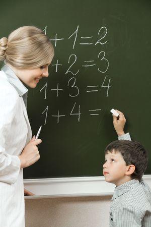 diligente: Retrato de alumno diligente buscando a su maestro cerca de la pizarra, mientras que haciendo sumas