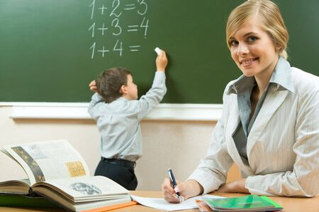 beautiful teacher: Portrait of pretty teacher sitting at the table on the background of schoolboy