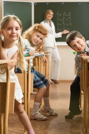 Image of curious schoolchildren sitting at the desk and looking at the camera in the classroom  photo