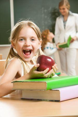 幸せな女子高生と本とテーブルに座って彼女の手でアップルの肖像画