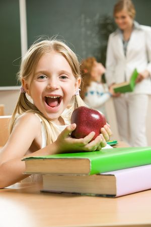 Portrait of happy schoolgirl and apple in her hands sitting at the table with books    photo