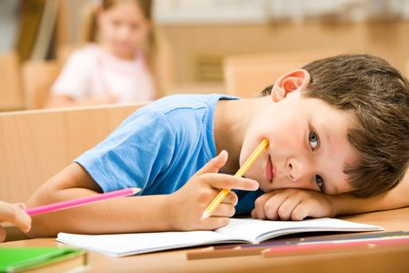 Close-up of tired pupil with yellow crayon putting his head on arm and looking at camera photo