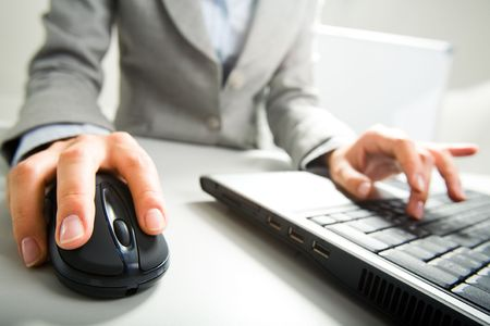Close-up of female hand on mouse while working on laptop